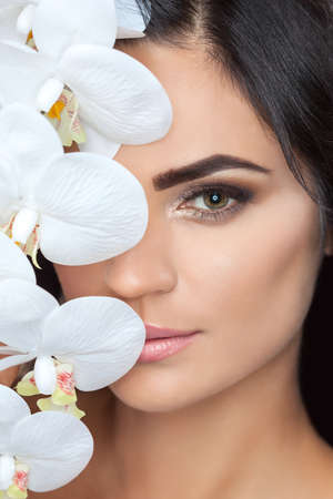 Portrait of a beautiful brunette woman with white orchid in her hand. Professional skin care and makeup.