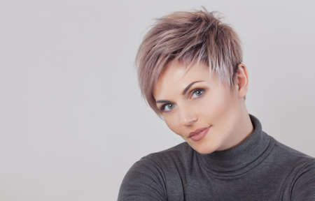 Portrait of a beautiful blonde woman with beautiful make-up and short haircut after dyeing hair in a hairdressing salon.