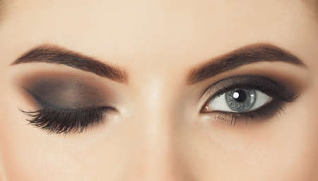 Hermosa mujer con pestañas largas y con hermoso maquillaje de noche. Ojos cerrados, un ojo cerrado y el otro abierto.