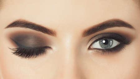 Mooie vrouw met lange wimpers en met mooie avond make-up. Ogen sluiten omhoog. Een oog is gesloten en het andere is open.