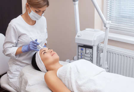 The doctor-cosmetologist makes the procedure treatment of Couperose of the facial skin of a beautiful, young woman in a beauty salon.Cosmetology and professional skin care.
