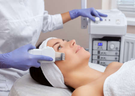 The doctor-cosmetologist makes the ultrasound cleaning procedure of the facial skin of a beautiful, young woman in a beauty salon. Cosmetology and professional skin care. Stock Photo