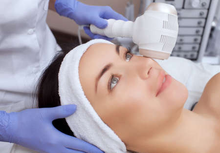 The doctor-cosmetologist makes the procedure Cryotherapy of the facial skin of a beautiful, young woman in a beauty salon.Cosmetology and professional skin care. 免版税图像