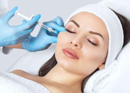 El médico cosmetólogo realiza el procedimiento de inyecciones faciales rejuvenecedoras para tensar y alisar las arrugas en la piel de la cara de una bella y joven mujer en un salón de belleza. Cuidado de la piel de cosmetología.