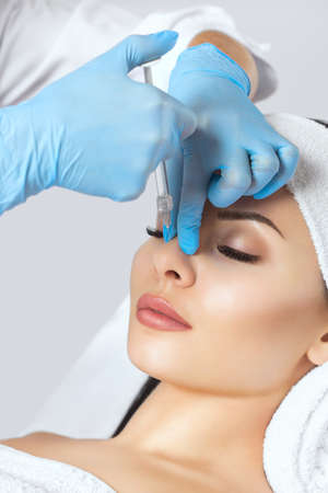 The doctor cosmetologist makes prick in the nose to correct the hump of a beautiful woman in a beauty salon. Cosmetology skin care. 版權商用圖片
