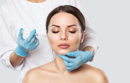 Lekarz kosmetolog wykonuje w gabinecie kosmetycznym Odmładzające ostrzykiwanie twarzy w celu ujędrnienia i wygładzenia zmarszczek na skórze twarzy pięknej, młodej kobiety w gabinecie kosmetycznym. Zdjęcie Seryjne