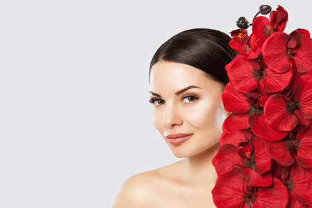 Portrait of a woman with beautiful make-up holds a red orchid in his hands. Professional makeup and skin care. Banco de Imagens - 120118290