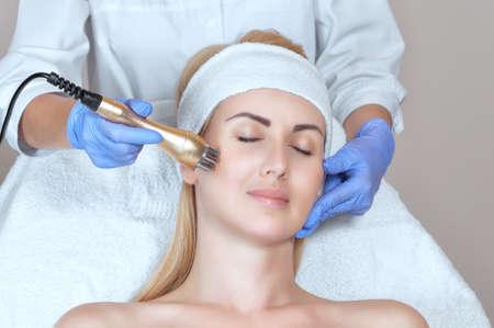 Retrato de mujer recibiendo levantamiento de rf en rostro y cuello. Procedimiento de lifting de radiofrecuencia en un salón de belleza.