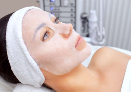The cosmetologist for procedure of cleansing and moisturizing the skin, applying a sheet mask to the face.Cosmetology and professional skin care. Stock Photo