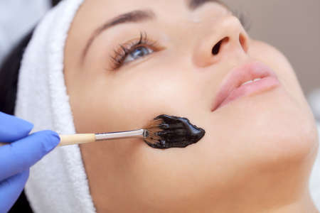 The procedure for applying a black mask to the face of a beautiful woman. Spa treatments and face care in the beauty salon.
