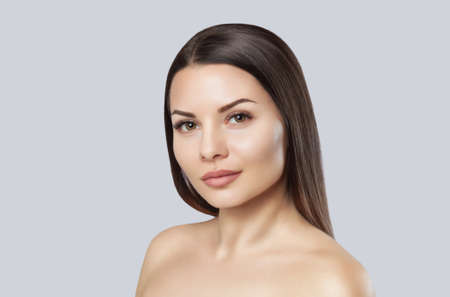 Portrait of a beautiful woman on a gray background. Professional makeup and skin care.