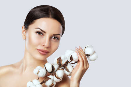 Portrait of a beautiful woman with cotton flower on a white background. Professional makeup and skin care. Stock Photo