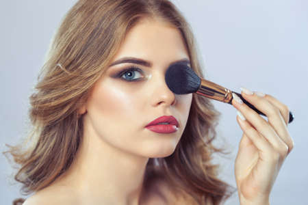 The Girl paints powder on the face, completes the smokey eyes make-up in the beauty salon. Professional skin care