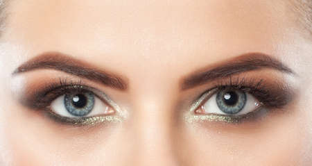 Beautiful woman with long eyelashes and with beautiful smoky eyes make-up. Eyes close up. Looking at the camera