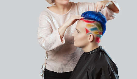 Hairdresser makes hairstyle.Portrait of a beautiful young teenager with a beautiful creative hairstyle, hair painted blue, yellow and red.