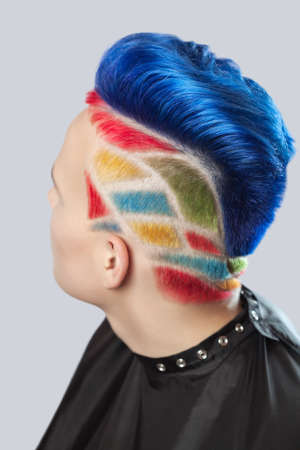 Portrait of a beautiful young teenager with a beautiful creative hairstyle, hair painted in blue, yellow and red.