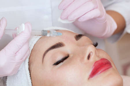 The cosmetologist makes the facial injections procedure for tightening and smoothing wrinkles on the face skin of a beautiful woman in a beauty salon.Cosmetology skin care.