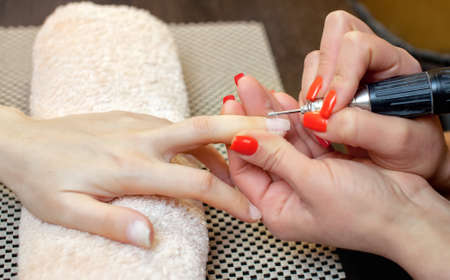 Nail artist saws and attaches a nail shape during the procedure of nail extensions with gel in the beauty salon. Professional care for hands.