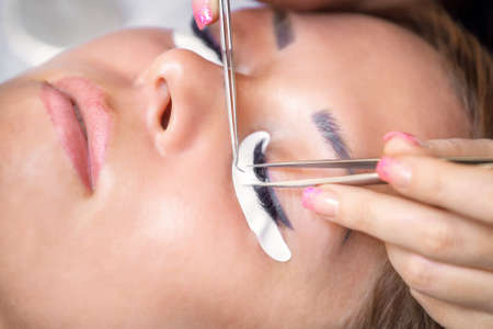 Eyelash extension procedure. Beautiful Woman with long lashes in a beauty salon. Stock fotó