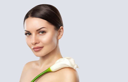 Portrait of a beautiful woman with Calla on a white background. Professional makeup and skin care.