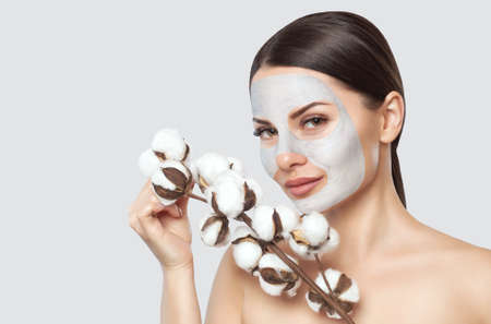 A beautiful young woman makes a moisturizing mask on her face, she is holding a cotton flower in her hands. Spa treatments and face care in the beauty salon.