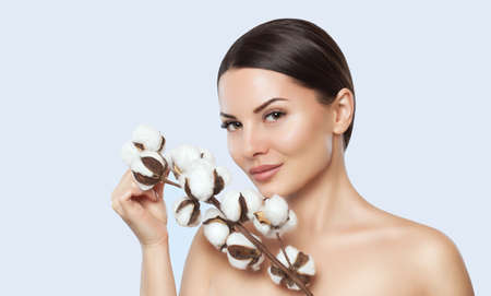 Portrait of a beautiful woman with cotton flower on a white background. Professional makeup and skin care. Stock fotó