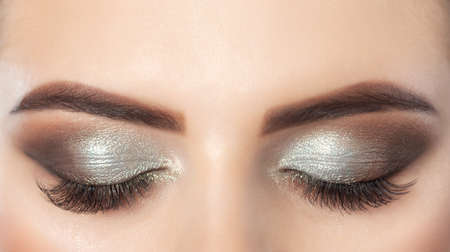 Beautiful woman with long eyelashes and with beautiful evening make-up. Closed eyes close up.