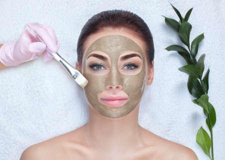 A beautiful woman makes a anti wrinkle mask on her face, she is holding a cotton flower in her hands. Spa treatments and face care in the beauty salon.