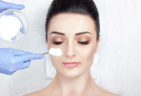 A beautiful woman makes a anti wrinkle mask on her face. Spa treatments and face care in the beauty salon.