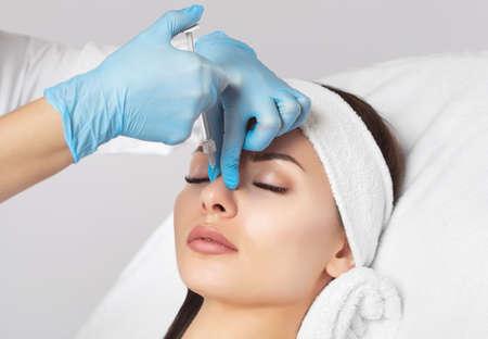 Lekarz kosmetolog robi ukłucie w nos, aby skorygować garb pięknej kobiety w salonie kosmetycznym. Kosmetyczna pielęgnacja skóry. Zdjęcie Seryjne