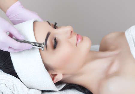 There is a woman, who is making the procedure Microdermabrasion of the facial skin in a beauty salon.Cosmetology and professional skin care. Standard-Bild - 131698779
