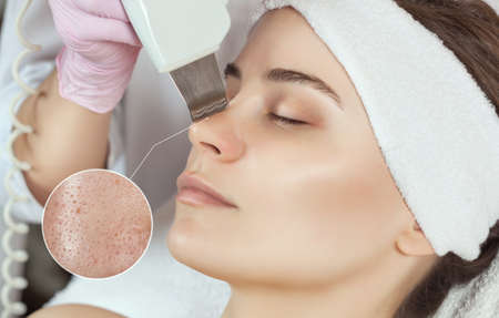 The doctor-cosmetologist makes the ultrasound cleaning procedure of the facial skin of a beautiful, young woman in a beauty salon. Cosmetology and professional skin care. Standard-Bild - 131698790