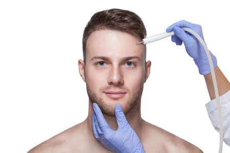 Cosmetologia maschile. L'estetista fa a un uomo una procedura per rimuovere l'acne dal viso. Archivio Fotografico
