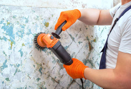 The builder holds in hands Angle grinder. Repair work, interior decoration of walls. Stockfoto