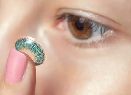 One woman holds a blue contact lens on her finger. Eye care and the choice between the means to improve vision. Standard-Bild - 131698915
