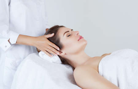 Masseur makes a relaxing massage on the face, neck and shoulders of a beautiful woman in a spa. Standard-Bild - 131698919