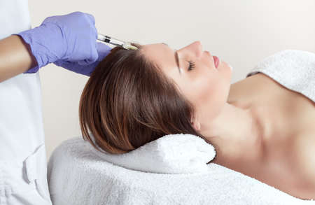 There is a woman and a cosmetologist, the woman is lying and the doctor is making the procedure of mesotherapy against hair loss and dandruff in a beauty salon.Strengthen hair and their growth. 版權商用圖片