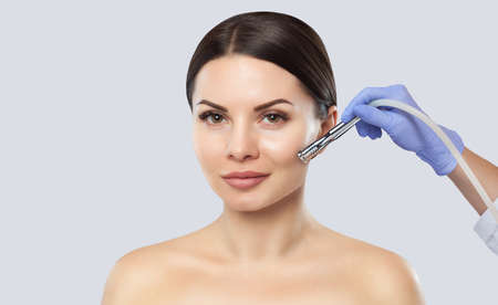 There is a woman, who is making the procedure Microdermabrasion of the facial skin in a beauty salon.Cosmetology and professional skin care.