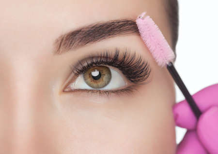 Beautiful Woman with long eyelashes in a beauty salon. Eyelash extension procedure. Lashes close up Stok Fotoğraf