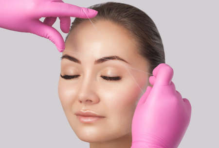 The make-up artist plucks eyebrows with a thread close-up. Face care, beauty treatments in the beauty salon.