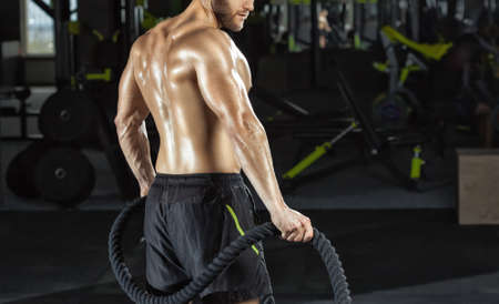 Muscular man does exercise with battle rope in the fitness gym. Sports concept, fat burning and healthy lifestyle.