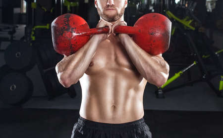 Muscular man lifts a heavy kettlebell during a workout in the gym. Sport concept, fat burning and healthy lifestyle. Imagens