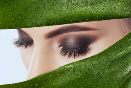 Beautiful Woman with long lashes on the background of a leaf of monstera with water droplets.Eyelash extension procedure. Cosmetology concept Stok Fotoğraf