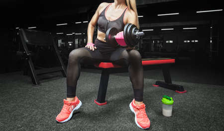 Slim, bodybuilder girl, lifts heavy dumbbell in the gym. Sport concept, fat burning and a healthy lifestyle.