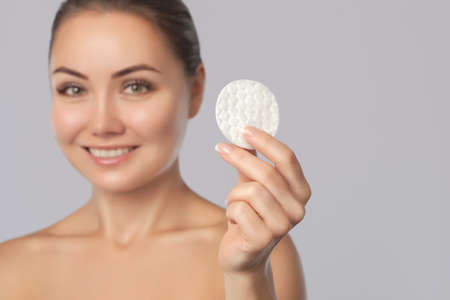 Beautiful smiling woman with clean skin holds a cotton pad. Womens skin care.