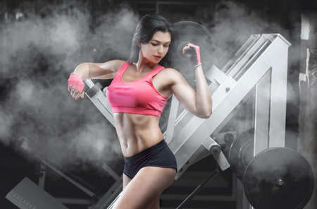 Slim, bodybuilder girl, does the exercises in the gym. Sport concept, fat burning and a healthy lifestyle.