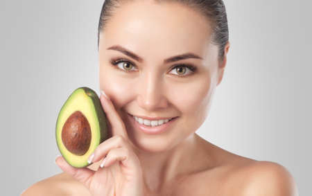 Beautiful smiling woman with clean skin holds ripe avocado near the face. Cosmetology skin care