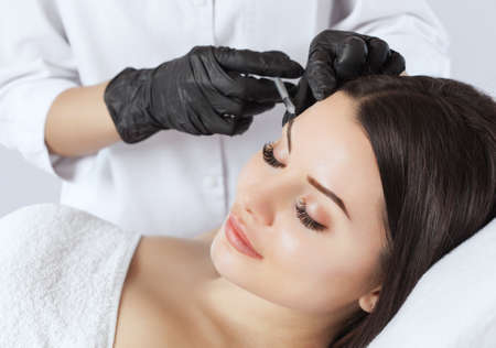 The doctor cosmetologist makes the Rejuvenating injections procedure for tightening and smoothing wrinkles on the face skin of a beautiful woman in a beauty salon.Cosmetology skin care.