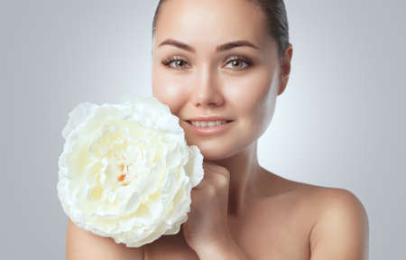 Portrait of a beautiful happy woman with clean skin on,She holds a beautiful white peony near her face.Cosmetology skin care Stok Fotoğraf
