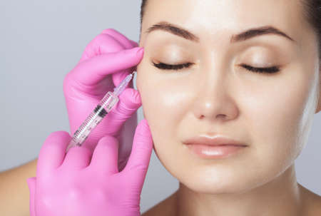 The doctor cosmetologist makes the Rejuvenating facial injections procedure for tightening and smoothing wrinkles on the face skin of a beautiful woman in a beauty salon.Cosmetology skin care.